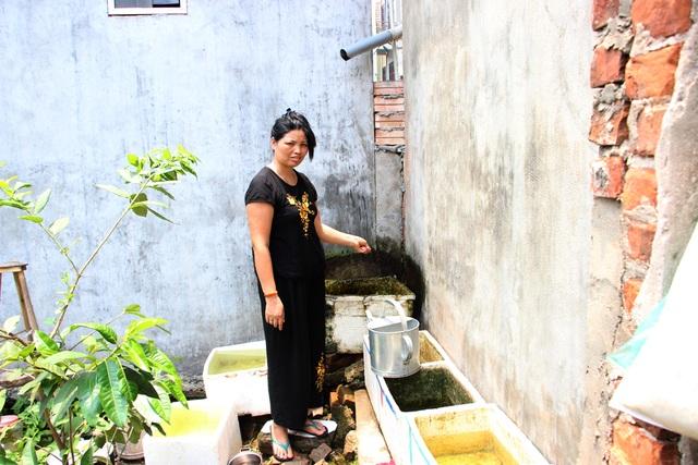 Bà Hương chỉ chỗ mà nhiều hộ dân trong xóm đã ra đây xin nước giếng khoan của nhà thờ bên cạnh.