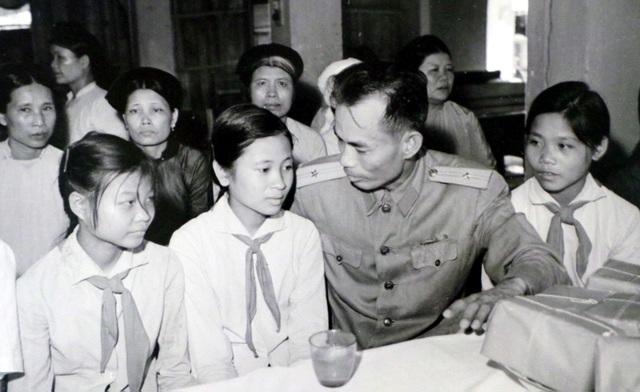 Đại diện lãnh đạo Bộ Quốc phòng thân mật nói chuyện với các cháu là con liệt sĩ được các tiểu thương chợ Đồng Xuân đỡ đầu (năm 1962).