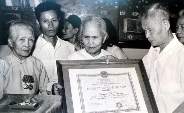 Đồng chí Lê Văn Lương, Ủy viên Trung ương Đảng, Bí thư Thành ủy Hà Nội, trao Huân chương Độc lập hạng Nhất cho cụ Nguyễn Thị Dương (ở Lý Nam Đế, quận Ba Đình) - người có 5 con là liệt sĩ (năm 1985).