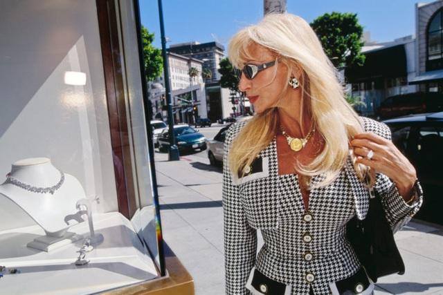 Một phụ nữ giàu có đang dạo bước để tìm kiếm những món đồ ở Rodeo Drive, Beverly Hills, Mỹ. Ảnh chụp năm 2000. Được biết, bên ngoài thành phố New York, Rodeo Drive là khu thương mại có giá thuê cao nhất ở Mỹ.