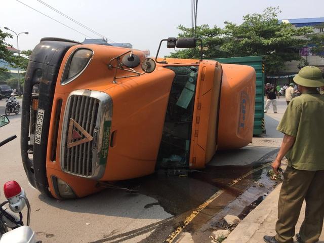 Chiếc xe container lật nghiêng, dầu chảy lênh láng, tài xế chỉ bị xây xát nhẹ. (Ảnh: Đức Văn)