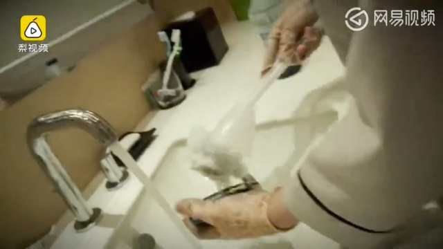 Nhân viên dọn vệ sinh ở khách sạn 5 sao dùng chổi cọ toilet để rửa cốc trong bồn rửa mặt