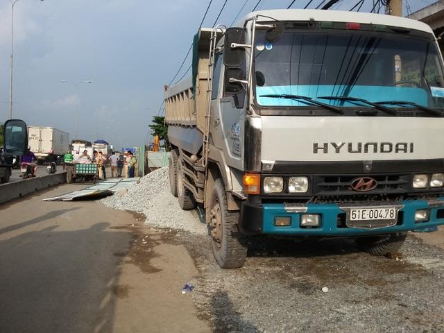 Chiếc xe ben đổ đá khiến đoạn rào chắn công trình bằng tôn ngã ra đường