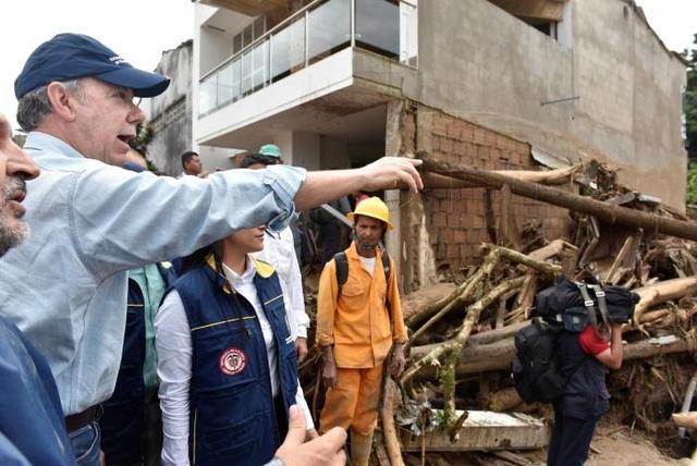 """""""Chúng tôi sẽ làm mọi cách để giúp đỡ họ. Vụ việc này khiến tôi rất đau xót"""", Tổng thống Colombia Juan Manuel Santos (mũ xanh) nói sau khi đáp chuyến bay tới Mocoa để khảo sát tình hình thiên tai. (Ảnh: Reuters)"""