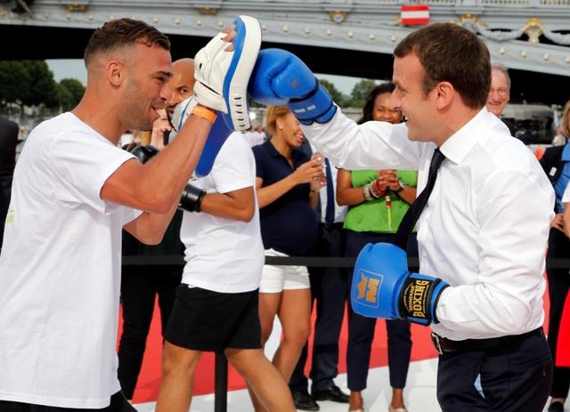 Tổng thống Macron đeo găng tay đấu quyền anh với một vận động viên (Ảnh: Reuters)