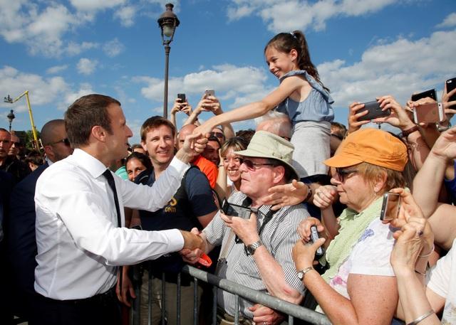 Tổng thống Macron bắt tay người dân khi tới khu vực tổ chức ngày hội Olympic tại Paris hôm 24/6 (Ảnh: Reuters)