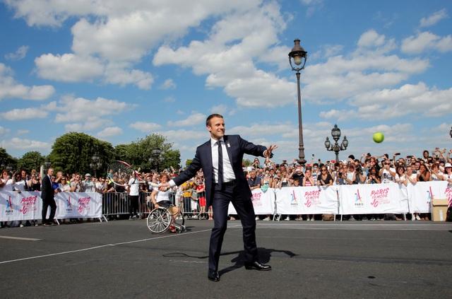 Tổng thống Macron mặc vest, cầm vợt thi đấu cùng các vận động viên quần vợt (Ảnh: Reuters)