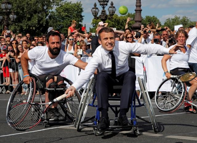 Ông Macron cởi áo vest, ngồi trên xe lăn chơi quần vợt với các vận động viên khuyết tật (Ảnh: Reuters)