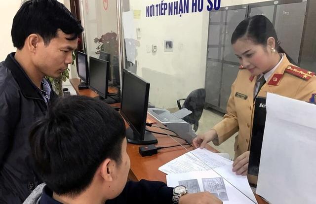 Đại úy Phạm Thị Lan Anh hướng dẫn người dân làm thủ tục đăng ký xe.