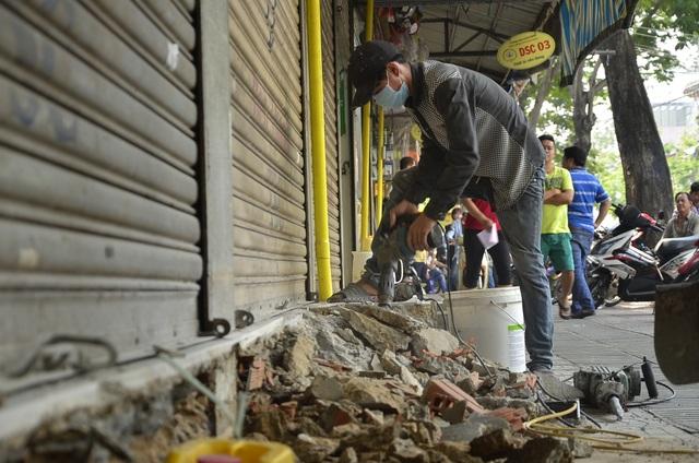Công nhân tiến hành đập bỏ bậc lên xuống mà tiểu thương xây trái phép quanh chợ Dân Sinh để trả lại vỉa hè cho người đi bộ