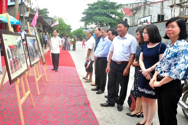 Người dân, cán bộ xem hình ảnh về thân thế, sự nghiệp của cố nhà báo Trần Kim Xuyến được BTC đặt tại con đường mới được đặt tên này.