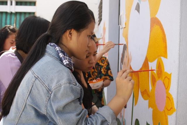 Học sinh thích thú tham gia vẽ tranh tường cùng thầy cô giáo.