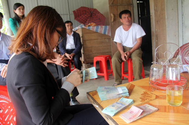 Cán bộ chi nhánh Ngân hàng Nông nghiệp huyện Vũ Quang làm thủ tục lập sổ tiết kiệm để số tiền các nhà hảo tâm quyên góp, giúp đỡ bé Quý được sử dụng lâu dài.