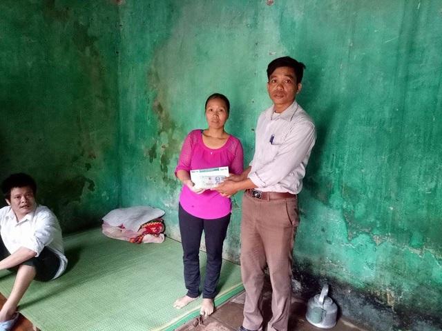 Đại diện chính quyền địa phương trao tiền bạn đọc ủng hộ đến gia đình anh Song