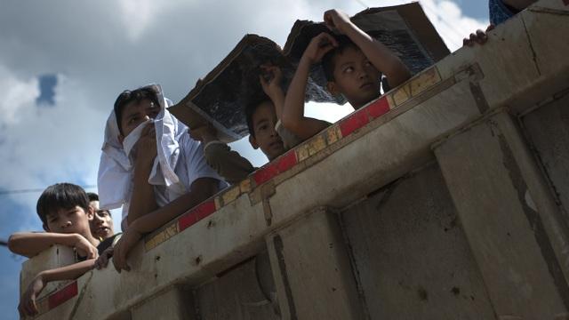 Lệnh ngừng bắn bị phá vỡ đã khiến 2.000 dân thường mắc kẹt và đối mặt với nhiều nguy cơ rủi ro khi chiến sự ngày càng ác liệt hơn. Trong ảnh: Trẻ em ngồi trên xe để sơ tán từ khu vực chiến sự tới nơi an toàn (Ảnh: Getty)