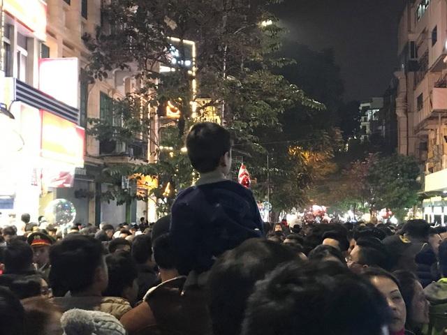 Các em nhỏ được ba mẹ cõng trên vai đứng xem lễ hội (Ảnh Trần Thanh)