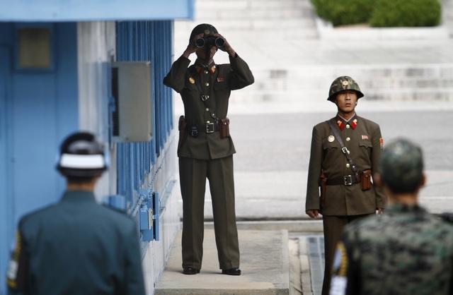 Binh sĩ Triều Tiên đứng gác cùng binh sĩ Hàn Quốc tại làng đình chiến Panmunjom ở Khu phi quân sự liên Triều (Ảnh: Reuters)