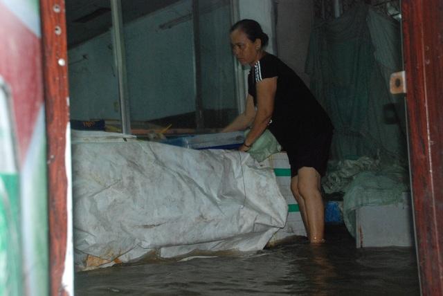Người dân phải dùng bạt chắn trước nhà để tránh nước tràn vào gây hư hỏng đồ đạc