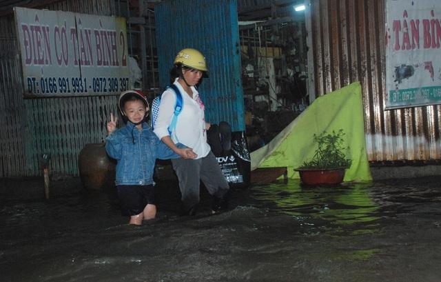 Em bé vui vẻ lội nước về nhà sau giờ tan trường