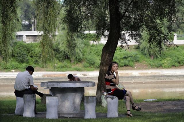 Người dân Triều Tiên nghỉ ngơi dưới bóng cây cạnh dòng sông Pothong.