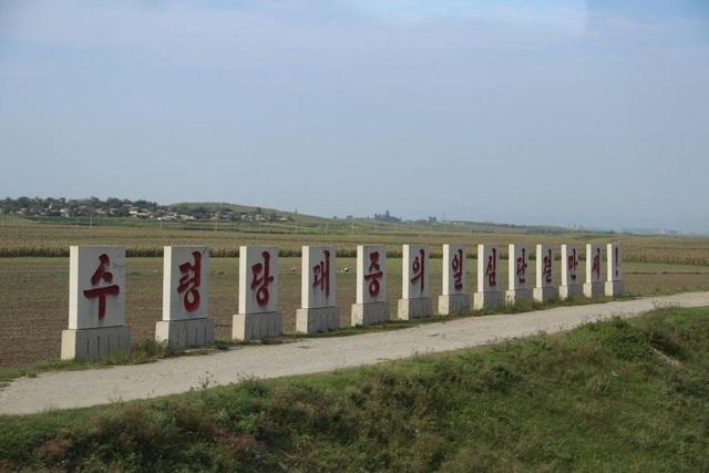"""Câu khẩu hiệu """"Lãnh đạo và quần chúng nhân dân mãi mãi đoàn kết"""" được in trên các cột màu trắng tại Triều Tiên."""