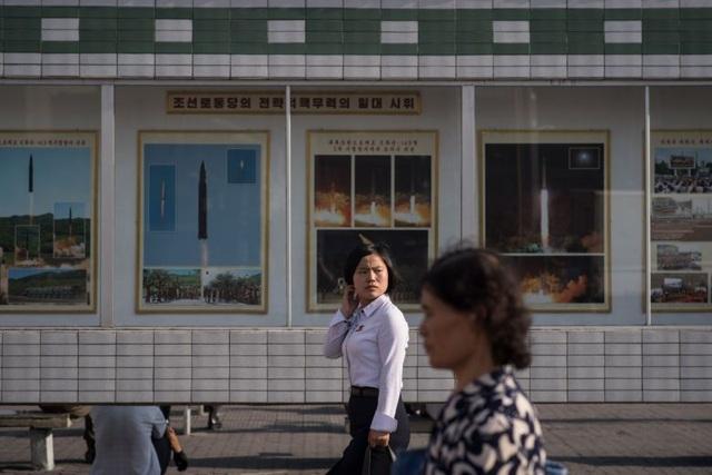 Một phụ nữ Triều Tiên bước qua bức ảnh ghi lại những vụ phóng tên lửa tại một nhà ga ở Bình Nhưỡng. (Ảnh: AFP)