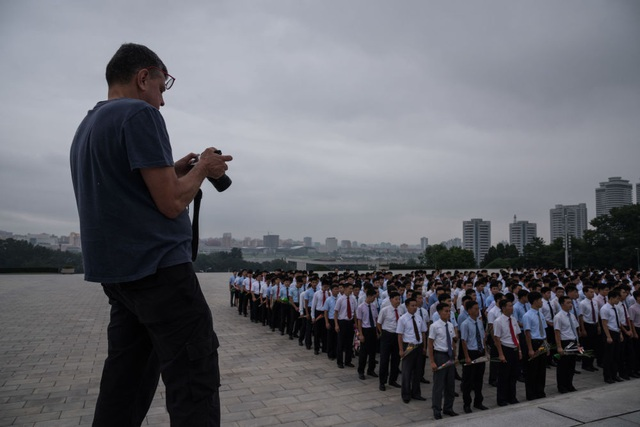 Khách du lịch nước ngoài chụp ảnh một nhóm công dân Triều Tiên đang cử hành nghi lễ trước tượng đài hai cố lãnh tụ Triều Tiên ở Bình Nhưỡng.