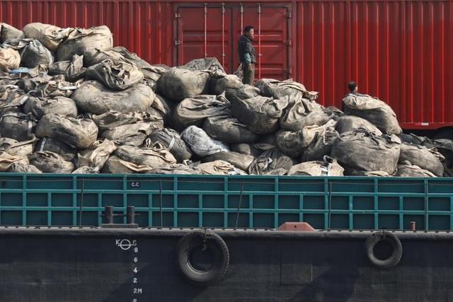 Nhân viên làm việc trên các bao tải hàng hóa được chuyển tới cảng ở gần khu vực Sinuiju của Triều Tiên.