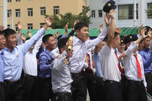 Người dân Triều Tiên ăn mừng khi theo dõi tin tức về vụ phóng tên lửa do truyền hình nhà nước chiếu trên một màn hình lớn đặt ở ngoài trời tại thủ đô Bình Nhưỡng vào sáng 29/7.