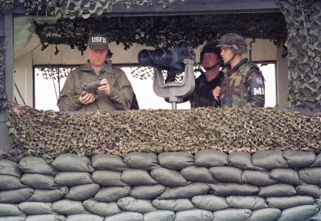 Cựu Tổng thống Bill Clinton dùng ống nhòm quan sát từ đài quan sát Ouellette (Ảnh: AP)