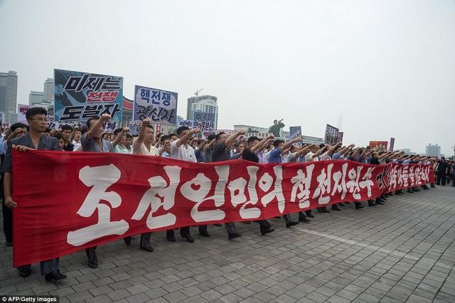 Những người tuần hành vừa hô khẩu hiệu vừa giơ nắm tay lên cao để thể hiện tinh thần quyết tâm của đất nước Triều Tiên (Ảnh: AFP)