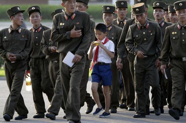 Một học sinh đi giữa một nhóm quân nhân sau khi kết thúc một ngày làm việc tại thủ đô của Triều Tiên ngày 25/7.