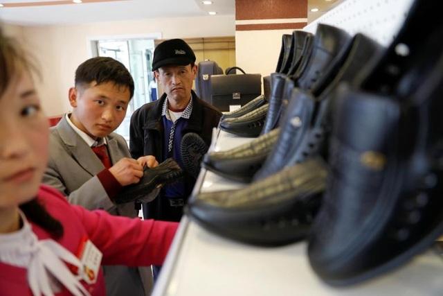 Báo cáo của Ngân hàng Trung ương Hàn Quốc mới đây cho biết tổng sản phẩm quốc nội (GDP) của Triều Tiên trong năm 2016 đạt mức 32.000 tỷ won (khoảng 28,5 tỷ USD), tăng 3,9% so với năm 2015. 2016 cũng là năm kinh tế Triều Tiên tăng trưởng mạnh nhất kể từ năm 1999. Trong ảnh: Khách hàng mua giày bên trong một cửa hàng ở thủ đô Bình Nhưỡng.