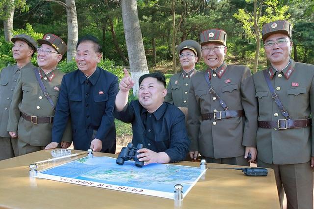 Các nhà khoa học tên lửa và hạt nhân đầu ngành của Triều Tiên đứng cạnh nhà lãnh đạo Kim Jong-un trong một vụ phóng thử tên lửa (Ảnh: KCNA)