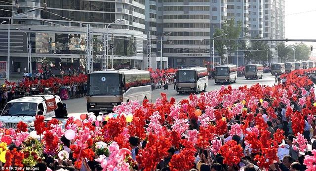 """Đưa tin về sự kiện ăn mừng thành công của vụ phóng tên lửa Hwasong-12 hôm nay, tờ Rodong Sinmun, cơ quan ngôn luận của đảng Cộng sản Triều Tiên, đăng tải bài viết trên trang nhất với tựa đề: """"Người dân nhiệt liệt chào đón các chiến sĩ khoa học quốc phòng"""". Trong ảnh: Những người dân xếp hàng hai bên đường chờ đón đoàn xe chở các nhà khoa học đi qua. (Ảnh: AFP)"""