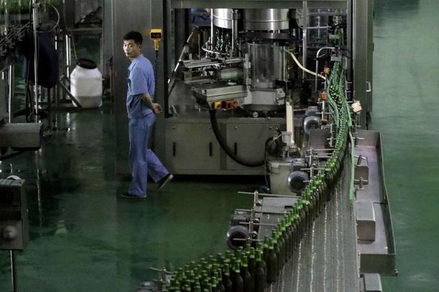 Han Hyong Chol, người phụ trách quản lý chất lượng của nhà máy bia Taedonggang, cho biết mỗi ngày nhà máy bia Taedonggang sản xuất khoảng 200.000 lít bia để đáp ứng nhu cầu của người tiêu thụ bia ở thủ đô Bình Nhưỡng - thành phố 3 triệu dân với khoảng 160 quán bia. Trong ảnh: Công nhân giám sát dây chuyền sản xuất bia tại nhà máy Taedonggang.