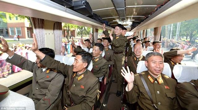 """""""Các tuyến đường tại thủ đô Bình Nhưỡng tràn ngập không khí tưng bừng của một ngày hội để chào đón các nhà khoa học của nền quốc phòng"""", hãng thông tấn quốc gia Triều Tiên (KCNA) đưa tin. Trong ảnh: Các nhà khoa học vẫy tay chào người dân ở thủ đô Bình Nhưỡng (Ảnh: AFP)"""