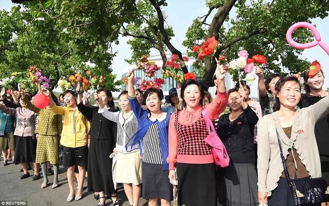 Sự hồ hởi, vui tươi hiện rõ trên gương mặt của những người dân Triều Tiên khi đón đoàn các nhà khoa học - những người góp công sức vào việc phát triển tên lửa Hwasong-12. (Ảnh: Reuters)