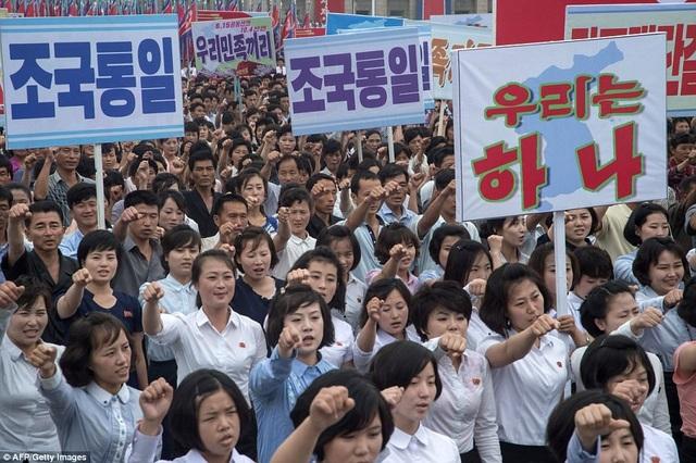 Đông đảo phụ nữ Triều Tiên tham gia tuần hành tại Quảng trường Kim Nhật Thành. Trên áo của mỗi người đều đeo huy hiệu in hình ảnh của các nhà lãnh đạo Triều Tiên. (Ảnh: AFP)