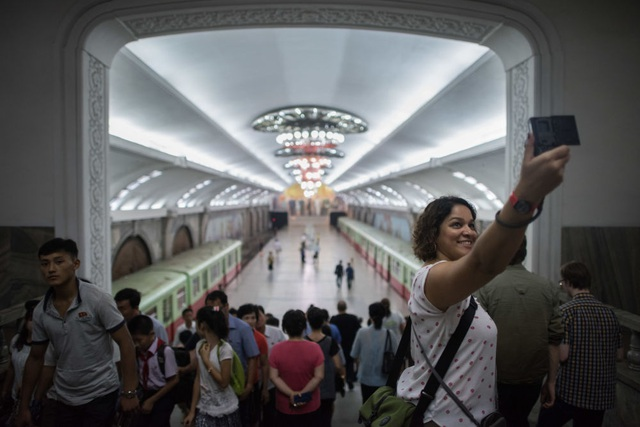 Khách du lịch nước ngoài chụp ảnh khi tới thăm nhà ga tàu điện ngầm ở Bình Nhưỡng.
