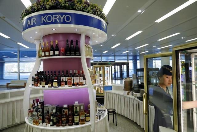 Chính phủ Triều Tiên cũng đang đẩy mạnh việc quảng cáo và bán các sản phẩm, đặc biệt là các sản phẩm nội địa của Triều Tiên cho khách du lịch tại sân bay để tăng nguồn thu. Trong ảnh: Một gian hàng bán đồ uống của hãng hàng không Air Koryo (Triều Tiên) tại sân bay Bình Nhưỡng.