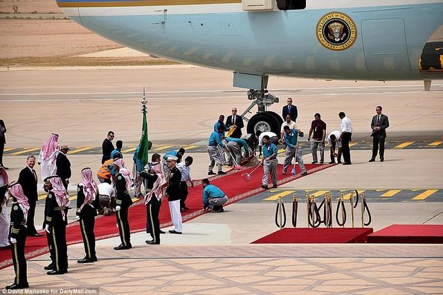 Các nhân viên tất bật chuẩn bị thảm đỏ trước khi nhà lãnh đạo Mỹ bước xuống từ chuyên cơ.