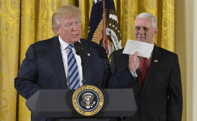 Tân Tổng thống Mỹ Donald Trump giơ bức thư của người tiền nhiệm Barack Obama trong lễ tuyên thệ tại Nhà Trắng ngày 22/1. (Ảnh: AFP)