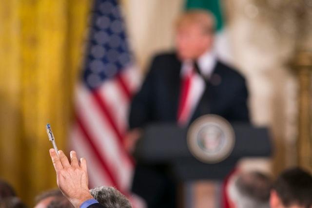 Một phóng viên giơ tay lên để đặt câu hỏi cho Tổng thống Trump trong một cuộc họp báo ở Nhà Trắng (Ảnh: New York Times)
