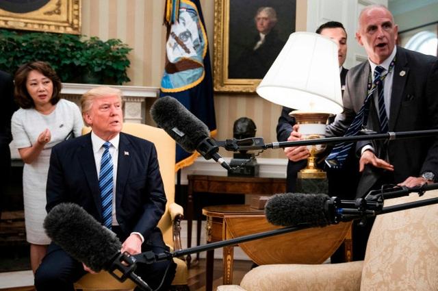 Tổng thống Trump phản ứng sau khi chiếc đèn đặt trên chiếc bàn cạnh ông suýt bị rơi vỡ trong lúc các phóng viên Hàn Quốc tác nghiệp (Ảnh: AFP)