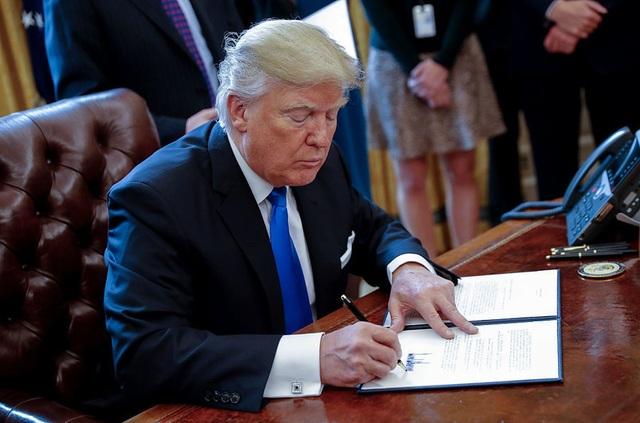 Tổng thống Donald Trump ký một sắc lệnh hành pháp tại Nhà Trắng hồi tháng 1 (Ảnh: NPR)
