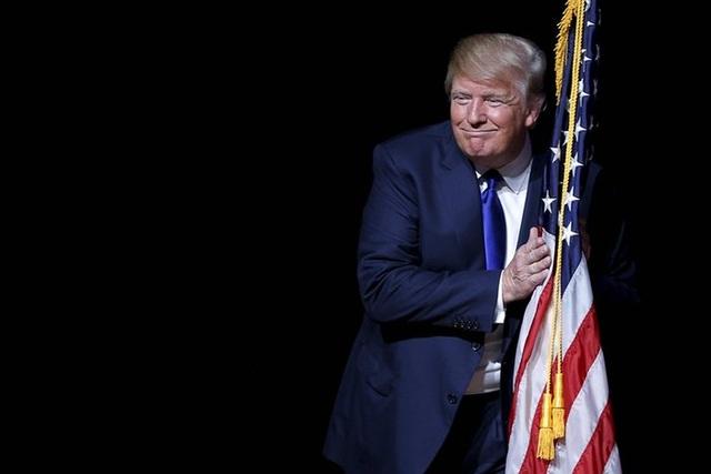 Là một người ngoại đạo trên vũ đài chính trị nhưng tỷ phú Trump đã từng bước vượt qua mọi rào cản để giành thắng lợi trong cuộc đua giành chiếc vé đại diện cho đảng Cộng hòa ra tranh cử Tổng thống. Ông đã vượt qua các cuộc bầu cử sơ bộ, đánh bại từng đối thủ đáng gờm nhất trong đảng của mình,bao gồm cả các chính trị gia nhiều kinh nghiệm. Trong ảnh: Ông Trump ôm cờ Mỹ trên sân khấu tại một sự kiện tranh cử ở Derry, New Hampshire Derry (Ảnh: Reuters)