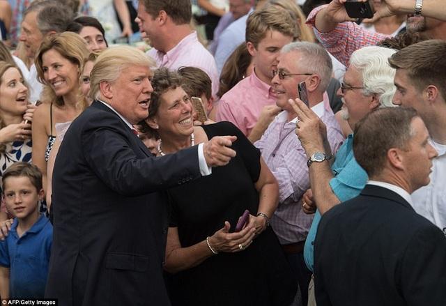 """Nhân sự kiện có sự tham dự của nhiều nghị sĩ đến từ hai đảng Dân chủ và Cộng hòa, Tổng thống Trump đã kêu gọi sự đoàn kết và thống nhất. Ông nói: """"Chúng tôi hy vọng rằng sự đoàn kết sẽ tiếp tục được tăng cường và phát triển giữa các nghị sĩ của hai đảng Dân chủ và Cộng hòa"""". Trong ảnh: Tổng thống Trump chụp ảnh cùng các vị khách dự bữa tiệc ngoài trời. (Ảnh: AFP)"""
