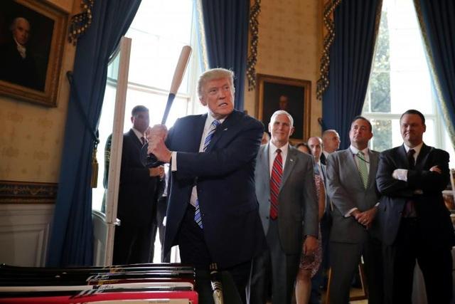 """Khi tới dự buổi triển lãm, nhà lãnh đạo Mỹ đã kêu gọi người dân ưu tiên sử dụng hàng hóa gắn mác """"Made in America"""" và đích thân quảng cáo cho một số sản phẩm. Trong ảnh: Tổng thống Trump cầm cây gậy bóng chày, một sản phẩm được trưng bày tại buổi triển lãm, trước sự chứng kiến của các quan chức Nhà Trắng và lãnh đạo các doanh nghiệp."""