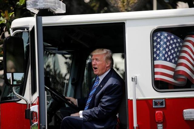 Tổng thống Trump cam kết sẽ đưa ra các điều chỉnh về pháp lý trong vòng 6 tháng tới để bảo vệ các doanh nghiệp sản xuất của Mỹ và xóa bỏ các rào cản thương mại cản trở hoạt động của các doanh nghiệp. Trong ảnh: Ông Trump ngồi trong một xe tải do Mỹ sản xuất sử dụng cho mục đích cứu hỏa được trưng bày tại buổi triển lãm ở Nhà Trắng.